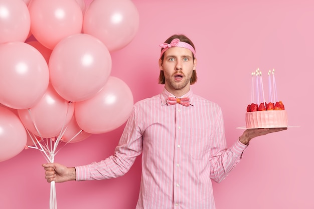 Surprised birthday man shocked to receive so many congratulations from friends and relatives poses with balloons and festive cake dressed in shirt bowtie headband isolated over pink wall