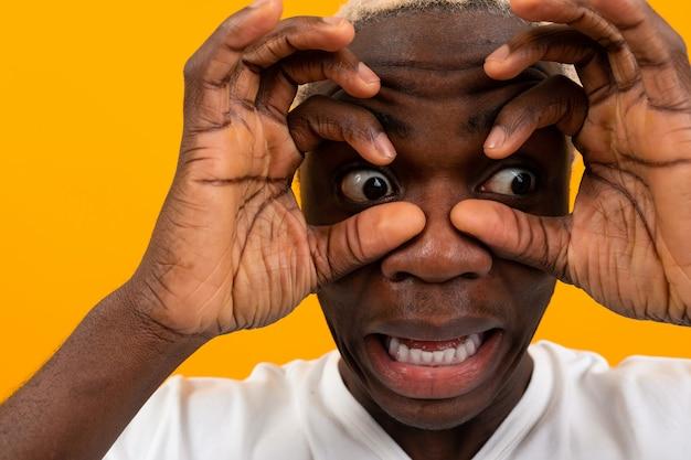 驚いた黒人アフリカの若者が顔を手で覆い、目を膨らませる
