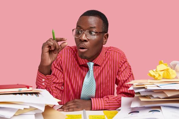 놀란 흑인 사업가가 작은 제스처를 취하고 낮은 수익으로 놀랐으며 분홍색 줄무늬 셔츠, 넥타이를 입고 문서 작업을 수행합니다.