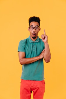 Surprised black man in big stylish glasses standing. cheerful guy in summer outfit posing with gently smile.