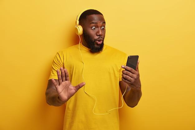 驚いた黒人男性のヒップスターがスマートフォンのデバイスを見つめる