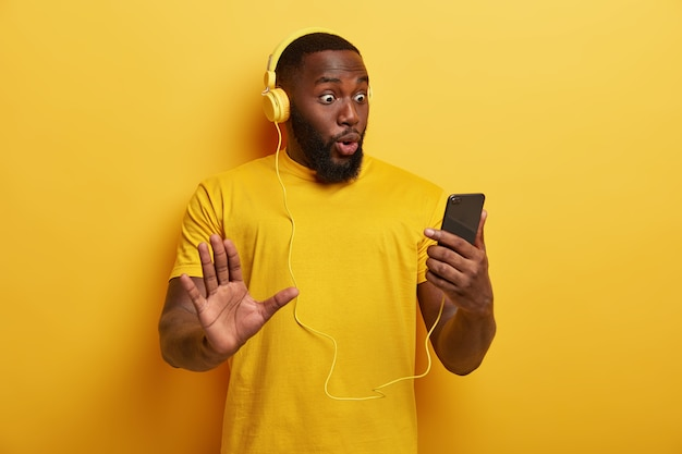 Surprised black man hipster stares at smartphone device