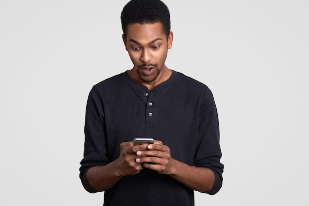 Surprised black man holds modern cellular, receives unexpected text message, surfs web page, dressed in casual clothes, feels shocked