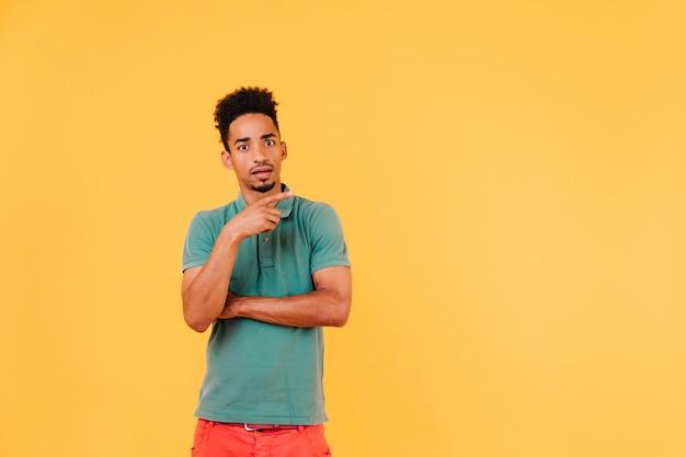 何かを考えて驚いた黒人男性。緑のtシャツを着た驚いた短髪の男の屋内写真。