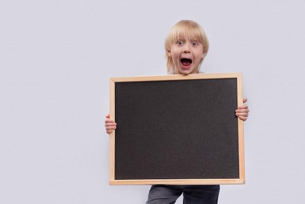 黒板を手で保持して驚いたの金髪の少年。コピースペース。テンプレート。モックアップ