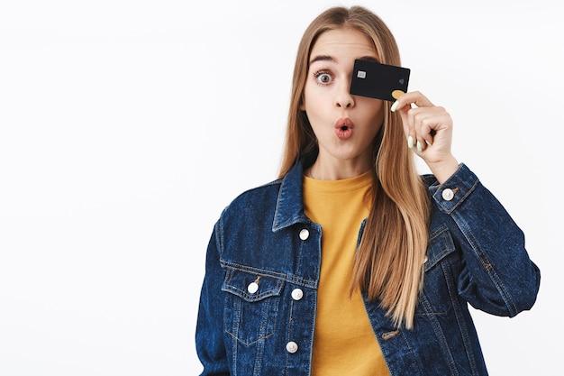 Удивленная белокурая девушка с изумлением держит кредитную карту над глазом, складывая губы, говорит: «вау», обнаружила отличные особенности новой банковской карты, используя онлайн-приложение, получила свою первую зарплату