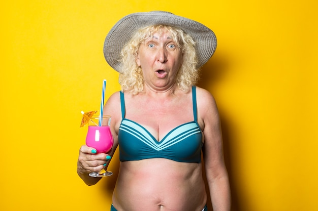 Surprised blond old woman in a swimsuit holding a cocktail on a yellow surface