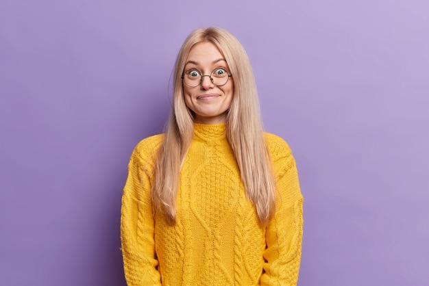 Удивленная белокурая европейская женщина с веселым выражением лица носит круглые очки, слышит неожиданные приятные новости, одетая в желтый свитер