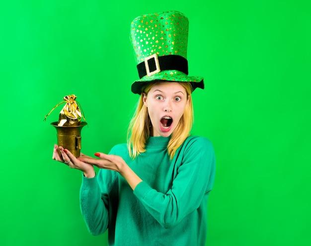 レプラコーンの衣装で驚いたブロンドの女の子は、ゴールドグリーンの帽子でポットを保持しますレプラコーンはでポットを保持します