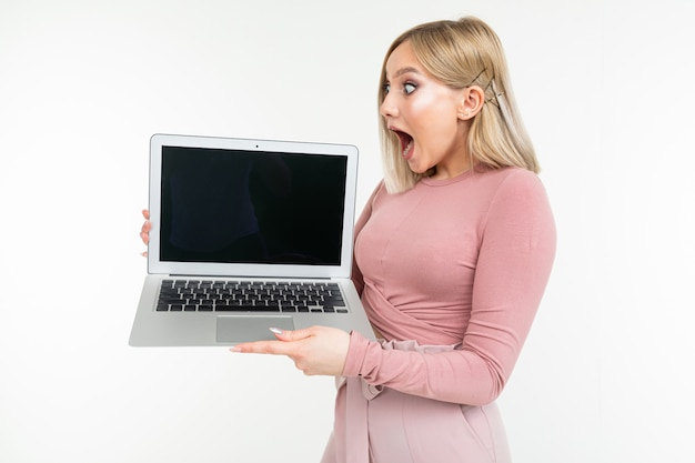Surprised blonde girl in pink clothes holds a laptop with the display forward with an empty blank on a white studio background