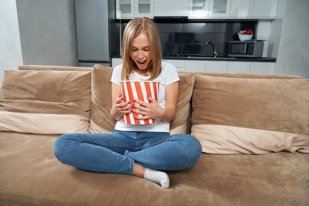 Удивленная блондинка смотрит полосатое ведро из попкорна