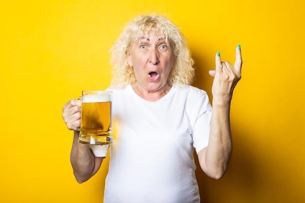 맥주 한 잔을 들고 로커 염소를 보여주는 놀란 금발 늙은 여자