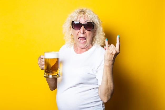맥주 한 잔을 들고 로커 염소를 보여주는 놀란 금발 늙은 여자 프리미엄 사진