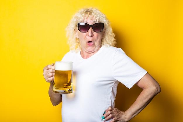 맥주 한 잔과 선글라스에 흰색 티셔츠에 놀란 금발 늙은 여자