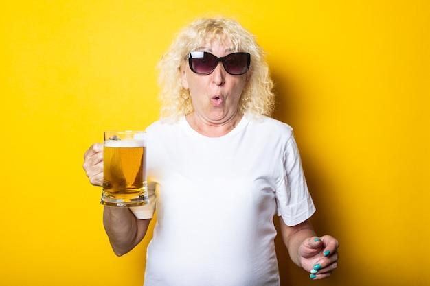 맥주 한 잔을 들고 선글라스에 놀란 된 금발 늙은 여자