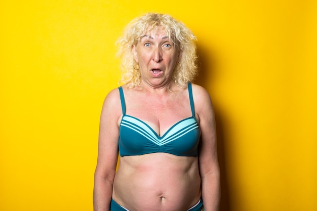 Surprised blonde old woman in swimsuit on bright yellow surface