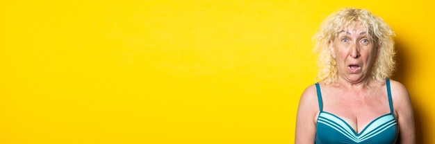 Surprised blonde old woman in a swimsuit on a bright yellow surface