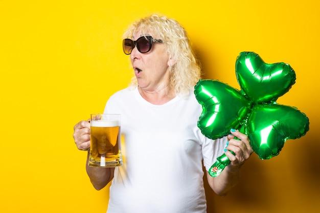 맥주 한 잔과 클로버 잎의 풍선 공기 풍선을 들고 놀란 금발의 늙은 여자
