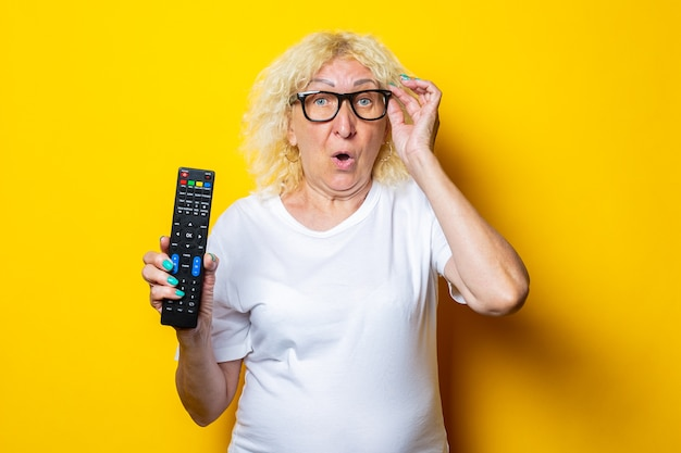 Surprised blonde old woman with glasses holding remote control