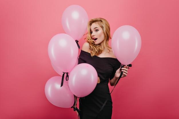Donna bionda sorpresa che tiene i bei palloncini del partito. amabile ragazza stupita in abito nero isolato sul muro rosa.