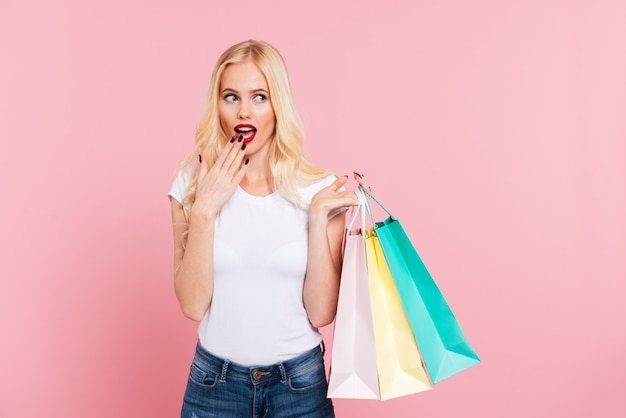 Surprised blonde woman holding packages while covering her mouth and looking away over pink