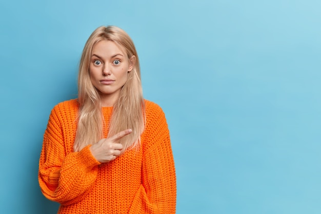 Surprised blonde woman points right on copy space on blue wall, expresses surprise