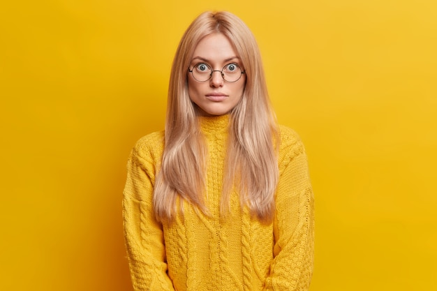 Surprised blonde woman stands speechless indoor wears round transparent glasses dressed in yellow sweater poses indoor. surprised impressed european female stares bugged eyes.