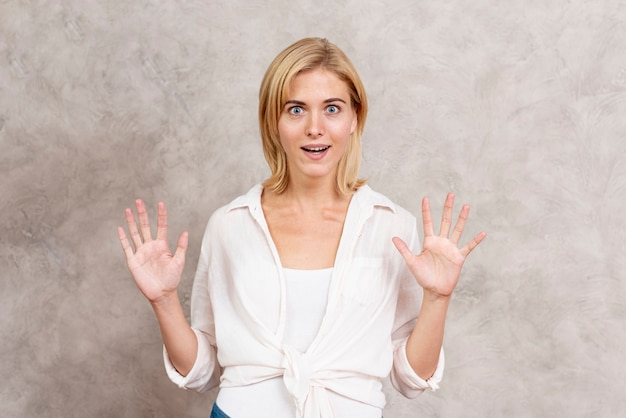 Surprised blonde woman with hands up