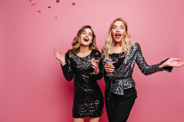 Donna bionda sorpresa con rossetto rosso in piedi sotto i coriandoli signore alla moda graziose in posa sul muro roseo durante la festa.