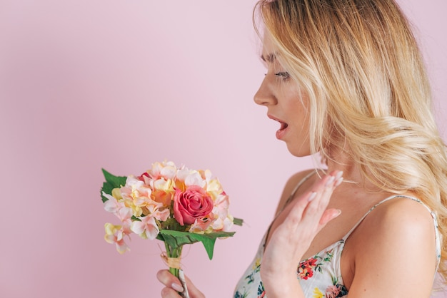 Surprised blonde young woman looked at colorful flower bouquet against pink background