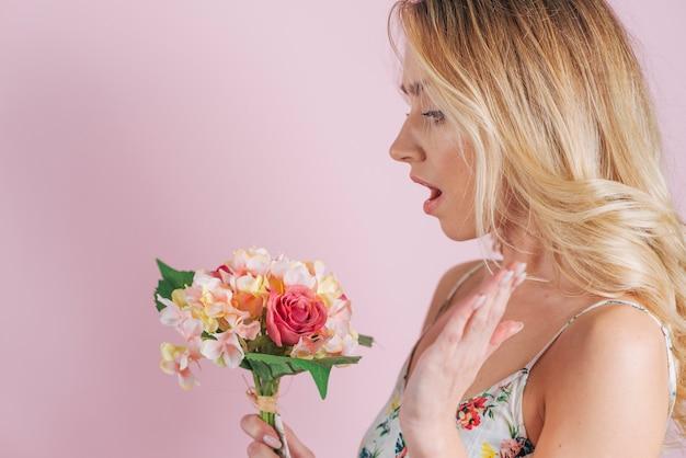 La giovane donna bionda sorpresa ha esaminato il mazzo variopinto del fiore contro fondo rosa