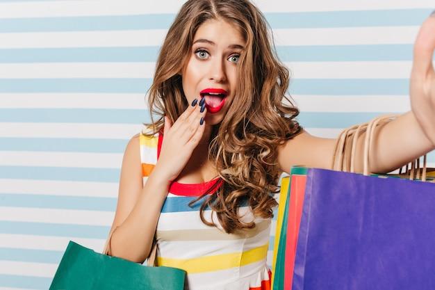 買い物の後に驚きを表現する驚いた青い目の女性。バッグとjocund白人女性の肖像画。