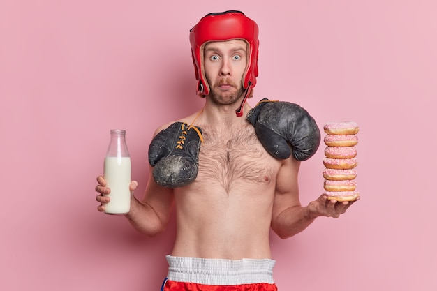 Surprised blue eyed man stares wears protective hat boxing gloves around neck has naked torso holds bottle of milk and pile of donuts has temptation to eat junk food