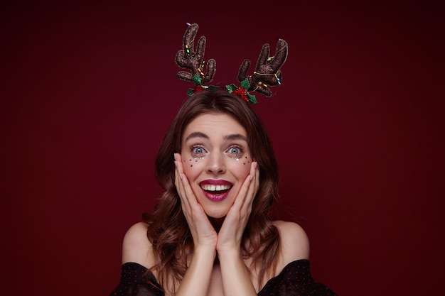 Удивленная голубоглазая молодая шатенка с вечерним макияжем, в праздничном обруче, смотрит широко открытыми глазами, держит ладони на щеках и широко улыбается