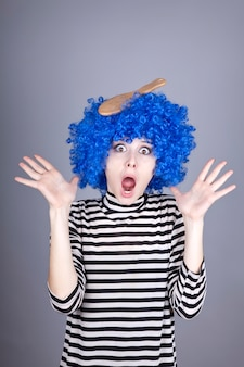 Surprised blue hair girl with stuck comb.