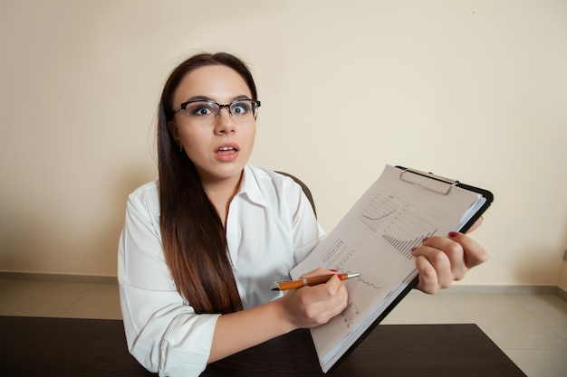 Surprised bookkeeper with accounting balance sheet