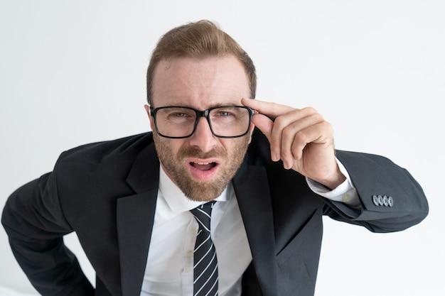 眼鏡を通してカメラを見つめている驚いたボス。驚くべきビジネスニュースのコンセプト。