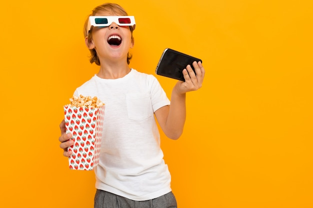 Surprised boy in glasses for a movie theater with popcorn and a phone on a yellow wall