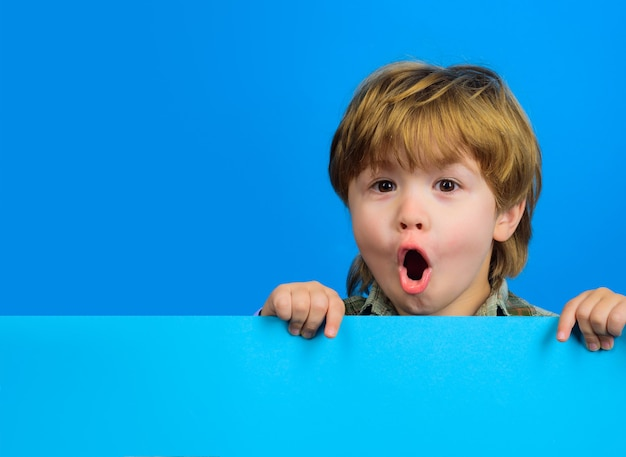 Удивленный мальчик держит пустую доску. ребенок держит пустой рекламный щит. маленький мальчик держит пустую рекламу.