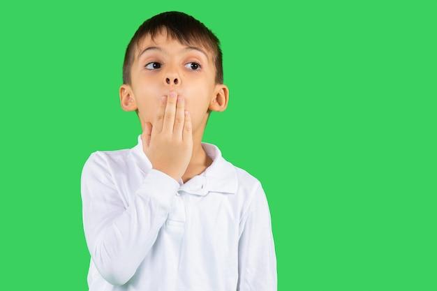 Удивленный мальчик подносит руку ко рту и смотрит в сторону