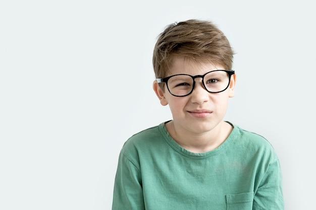 녹색 티셔츠와 안경에 놀란 소년 잠겨있는 그의 머리를 긁적