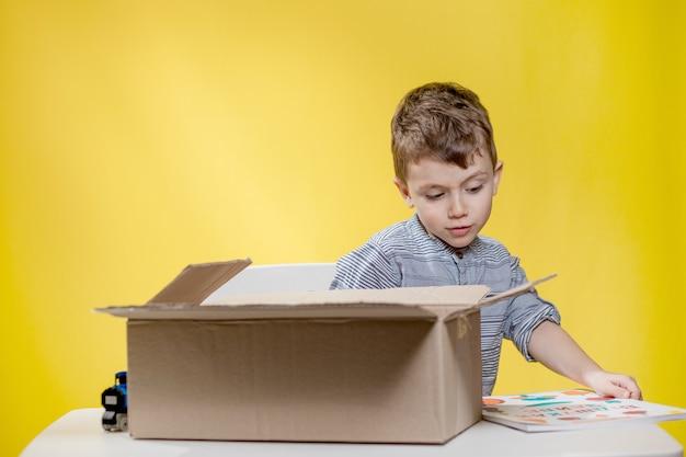 開封したvlogを記録しているときに、箱を開けて箱の中身を見て驚いてあえぎながら見ている驚いた少年。