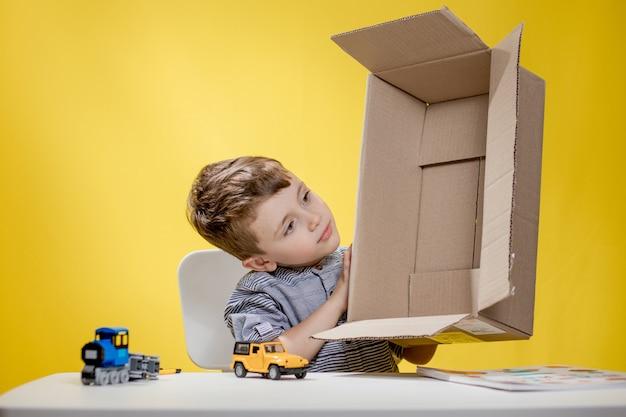 箱を開けて、箱を開けるvlogを記録している間、箱の中身を見て驚いてあえぎながら見ている驚いた少年。