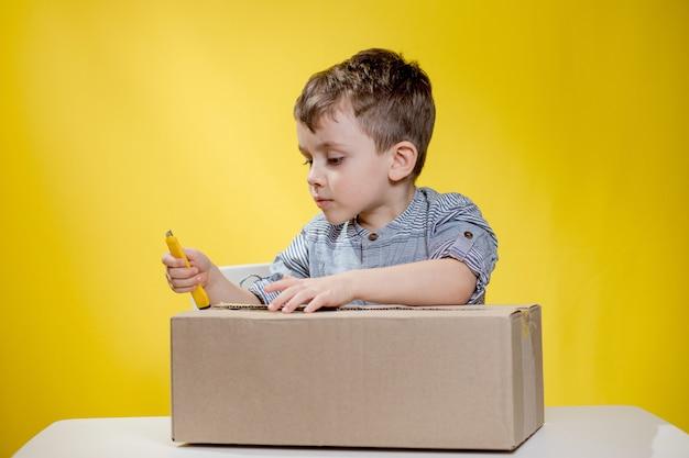 Удивленный мальчик, открывающий коробку и задыхающийся от удивления, видя содержимое коробки во время записи видеоблога с распаковкой.
