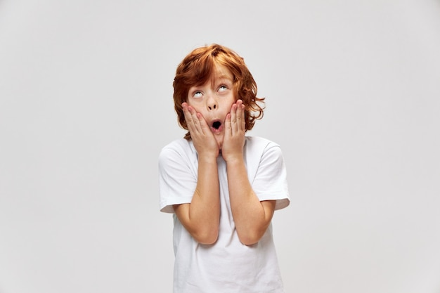 Surprised boy looking up with open mouth gray background