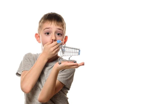 Удивленный мальчик зажал рот рукой, держа на ладони небольшую металлическую тележку для покупок.
