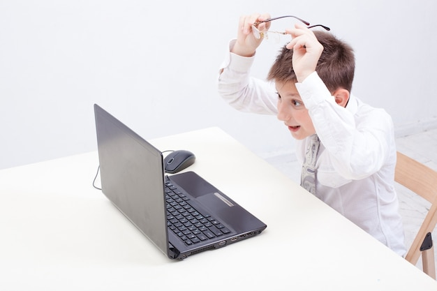 The surprised  boy using his laptop computer on white background.