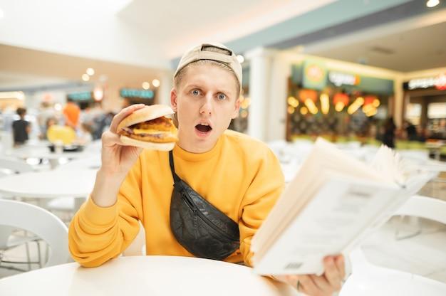 ハンバーガーと本を手に持った驚いた少年がレストランに座ってカメラを見ている