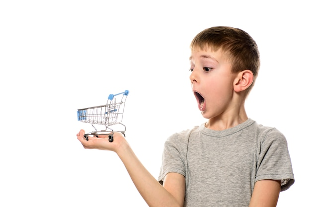 Surprised boy with open mouth holding a small metal shopping cart on a palm. isolate on white