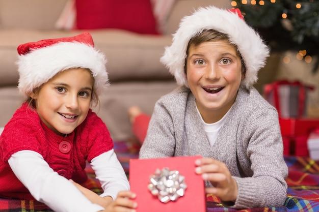驚いた兄とサンタ帽子の妹の贈り物を開く